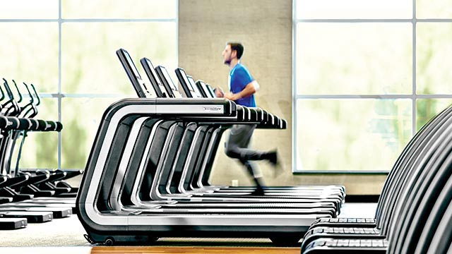 A man running on a treadmill, with a large, high-tech display