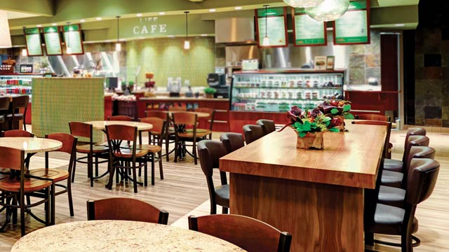 Tables and chairs at a LifeCafe, with menus and grab-and-go items in the background