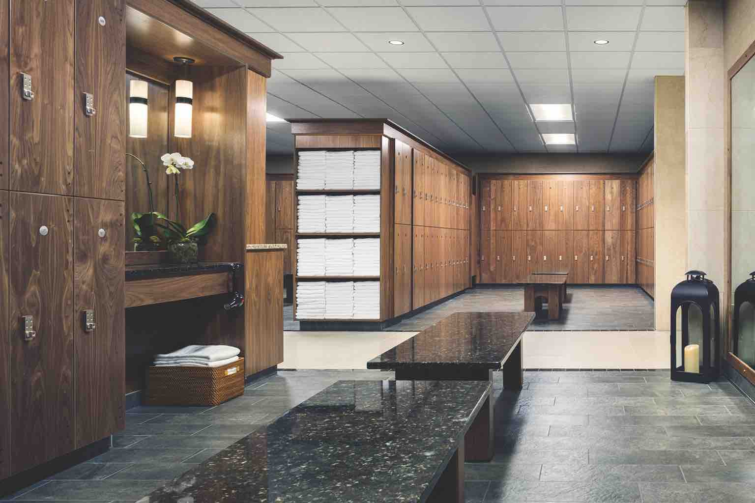 A luxurious locker room with rows of wooden lockers, a vanity area, benches and open shelving with stacks of white towels
