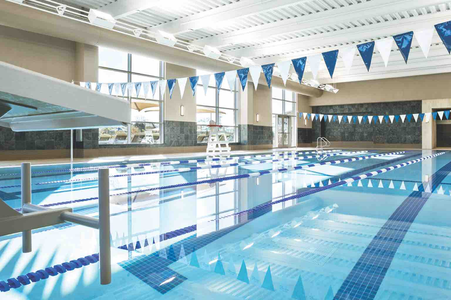 A brightly lit indoor lap pool with blue and white banners strung overhead