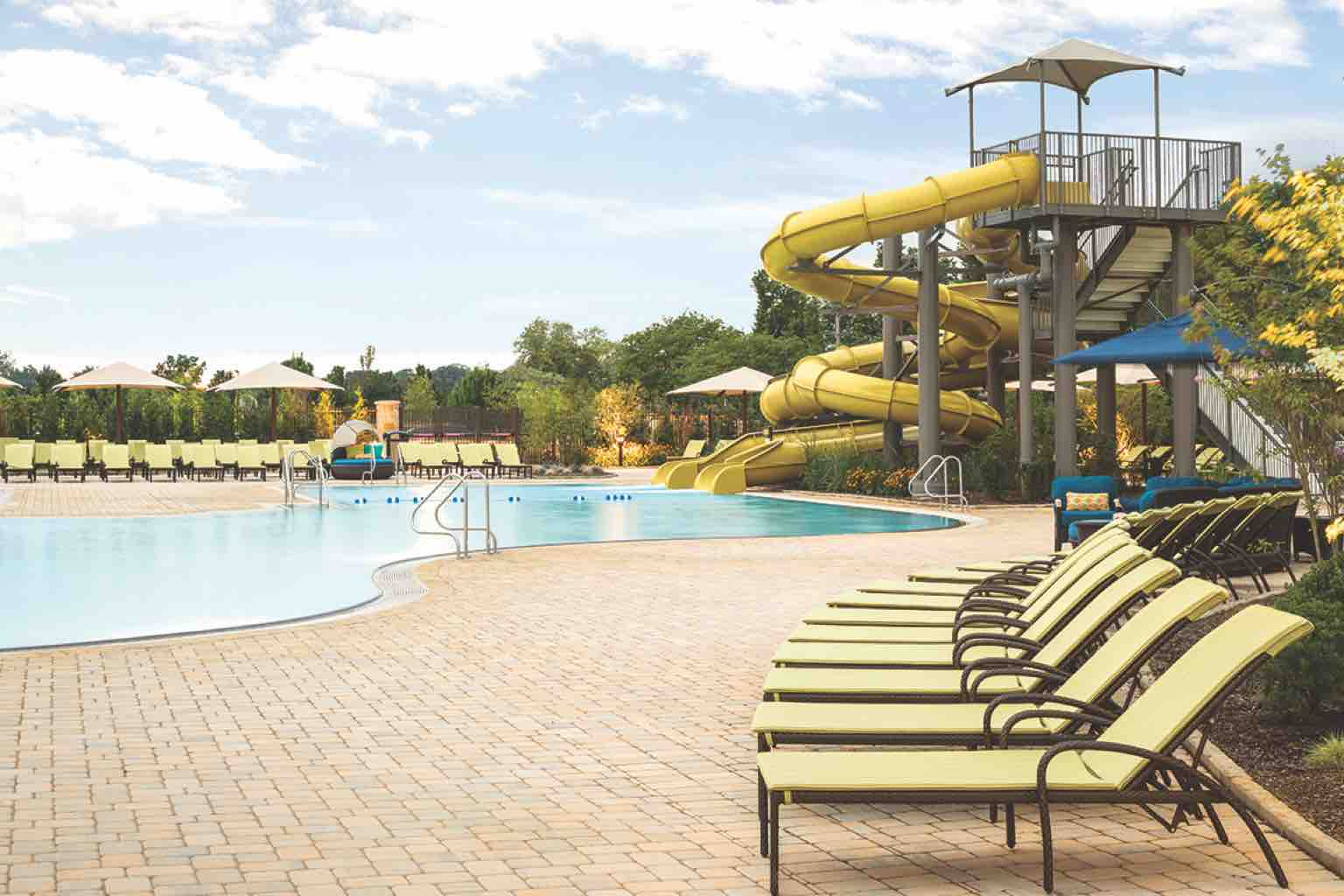 An outdoor pool deck with a chaise-lined pool, umbrellas and two-story waterslide