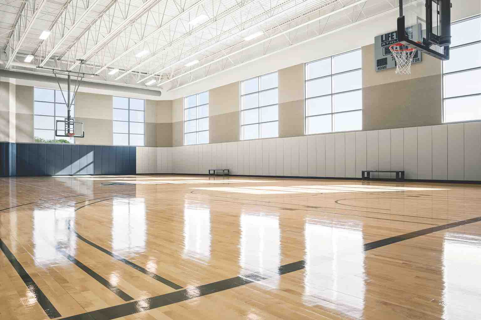 A spacious gym with a gleaming wood floor, basketball hoops and large, sun-filled windows