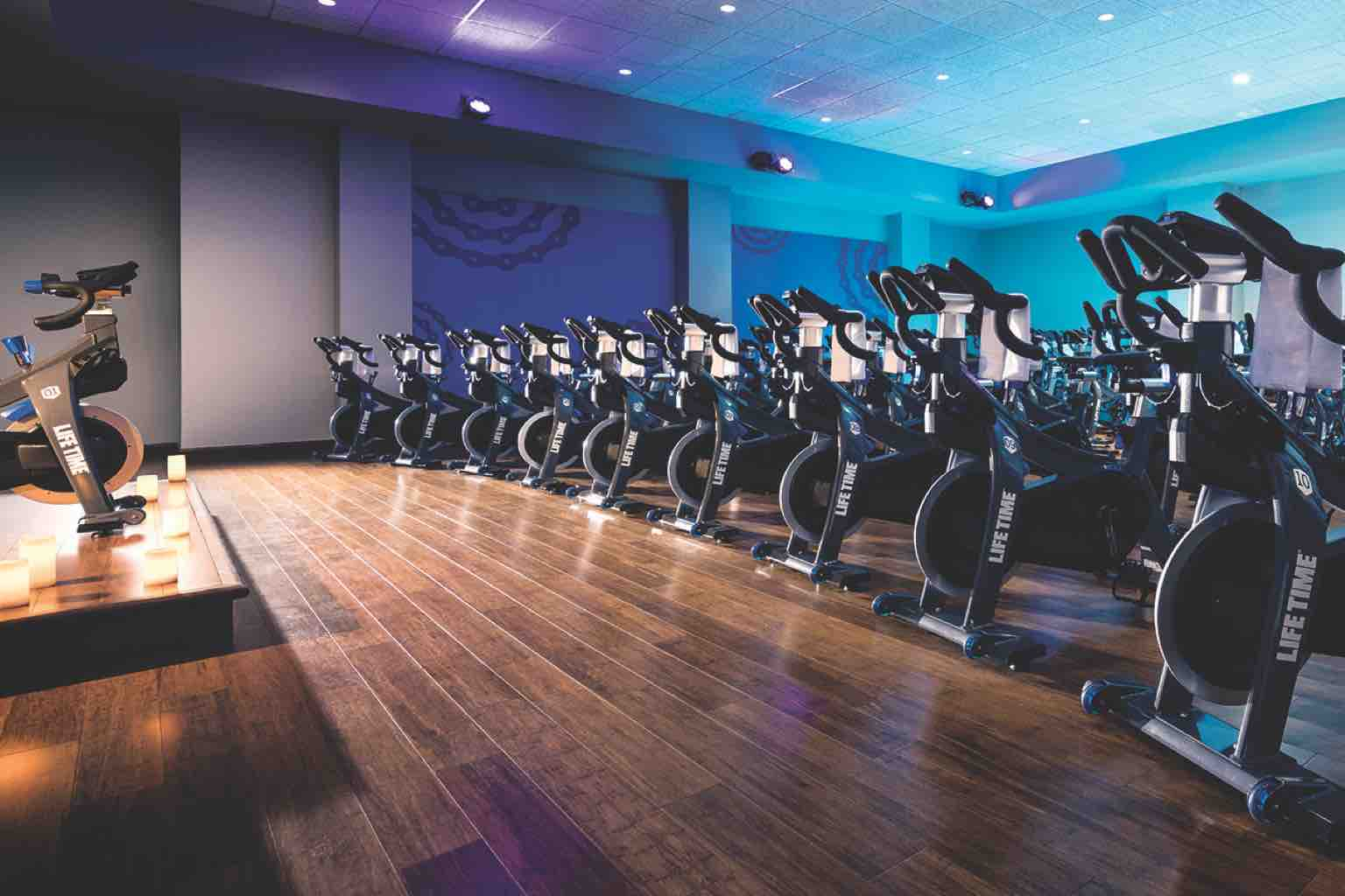 Rows of state-of-the-art stationary bikes face the instructor's platform in a purple- and blue-lit cycle studio