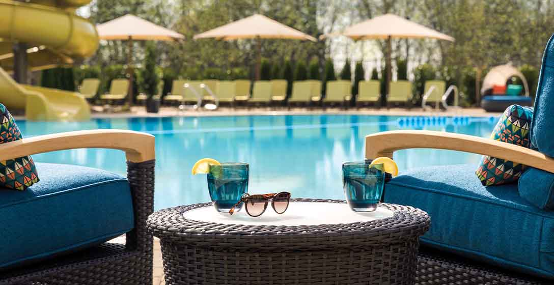 2 chairs, a table with drinks and sunglass, overlook a Life Time Outdoor Pool