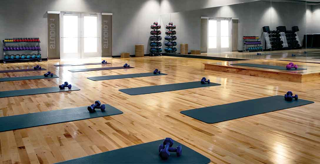 Yoga mats and dumbbells laid out in rows at a Life Time Studio