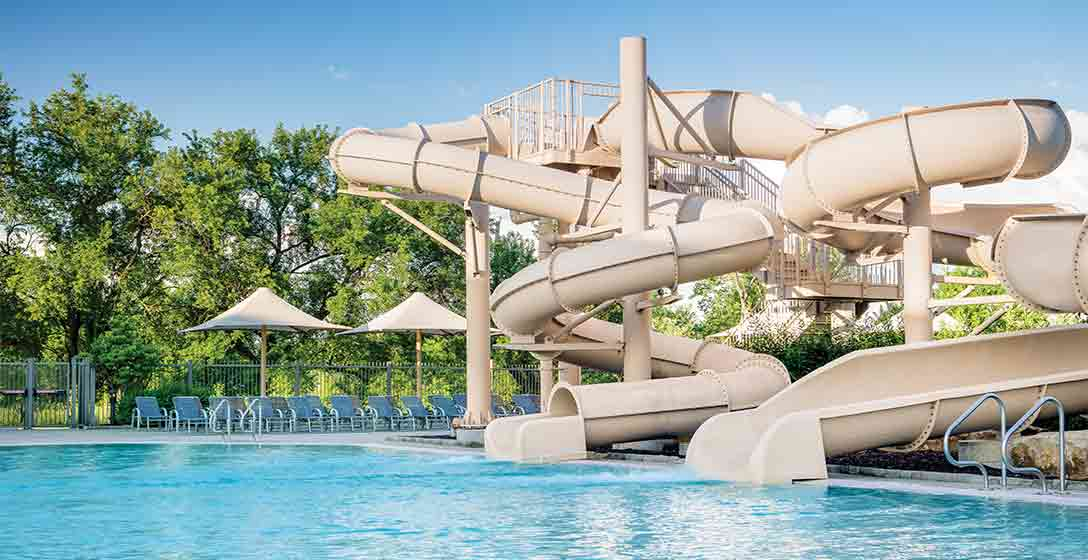 The leisure pool and waterslides at a Life Time Outdoor Pool