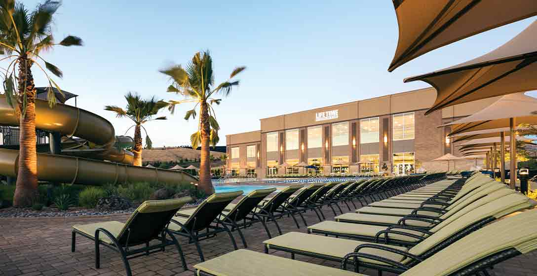 Lounge chairs around the leisure pool and waterslides at a Life Time Outdoor Pool