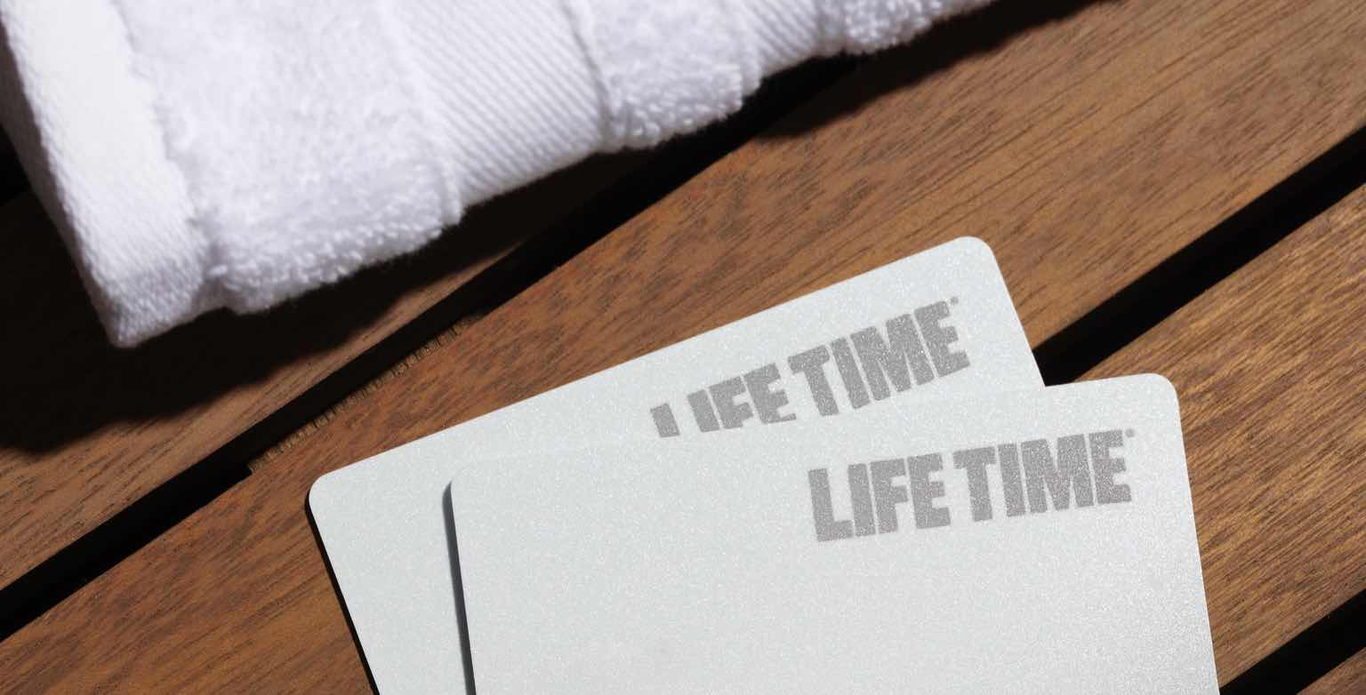 A photo of two Life Time 23rd St. membership cards on a wooden bench.