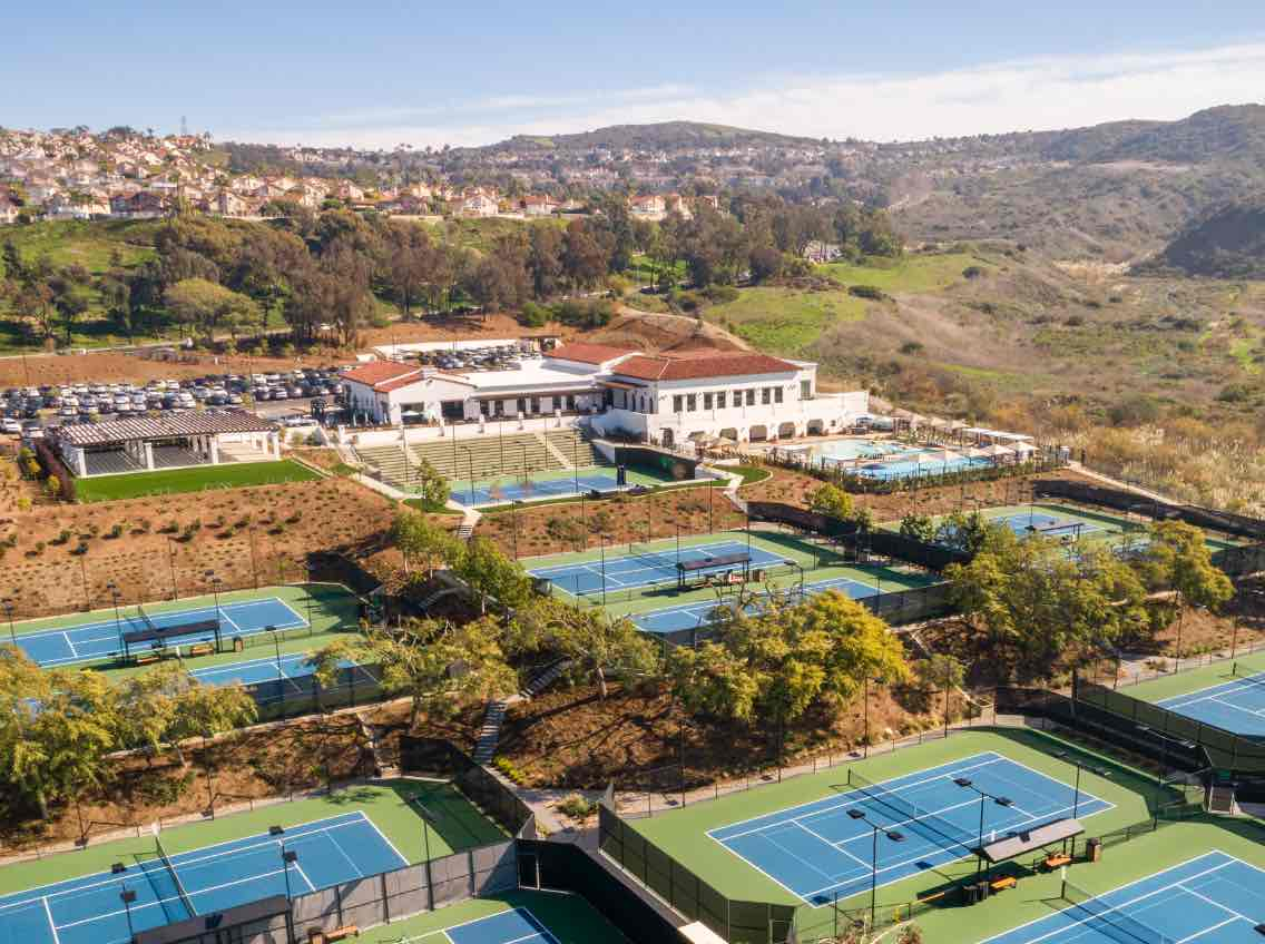 aerial view of many outdoor tennis courts nestled in the hillside