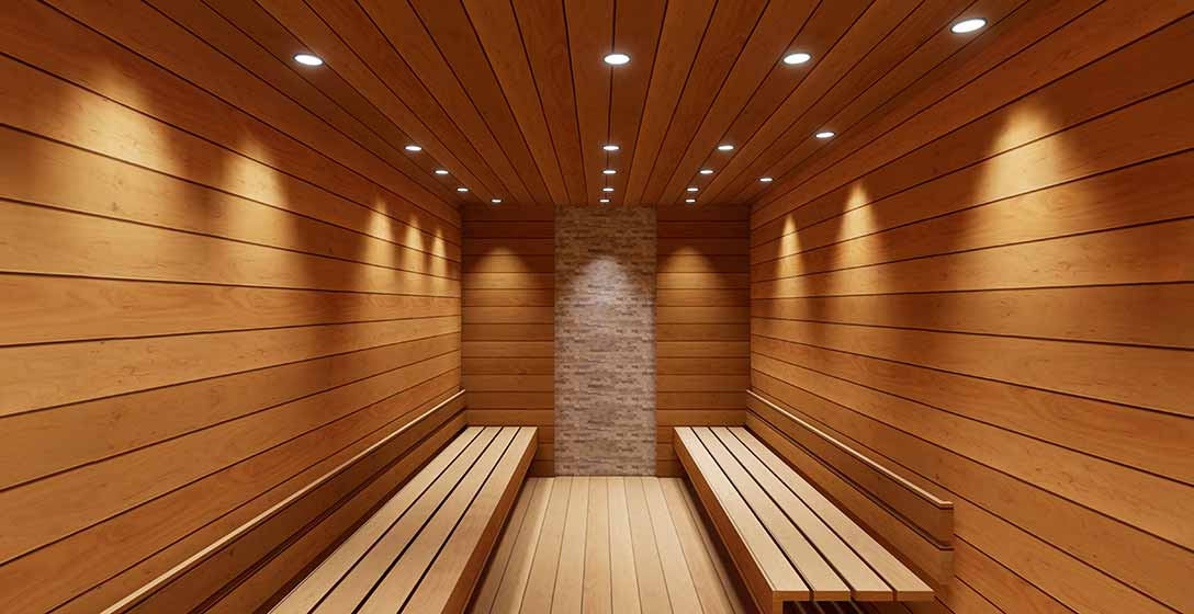 Inside the sauna with all wood walls and benching