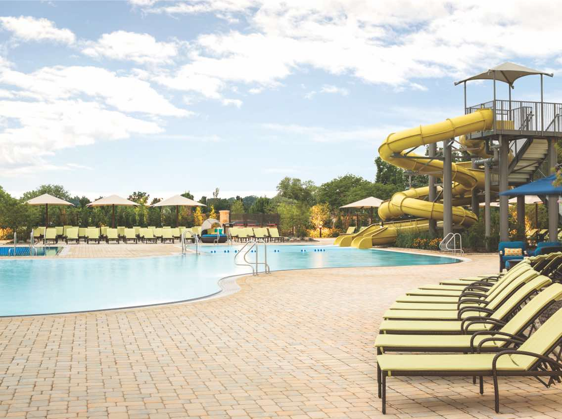 Outdoor pool area at Life Time with rows of lounge chairs and waterslide