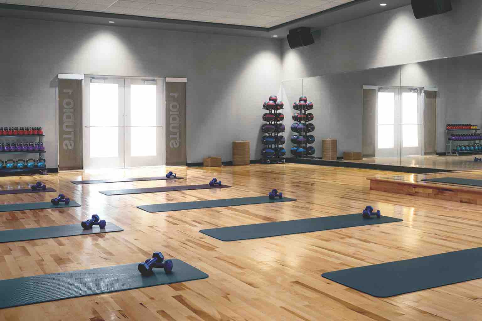 Blue yoga mats, each equipped with a set of hand weights, lined up on a studio's wood floor