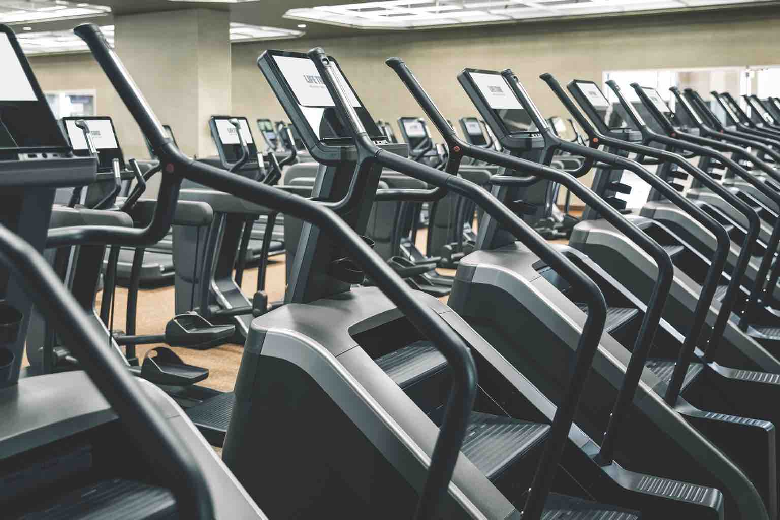 Rows of cardio machines lined up on the fitness floor at Life Time Flat Irons