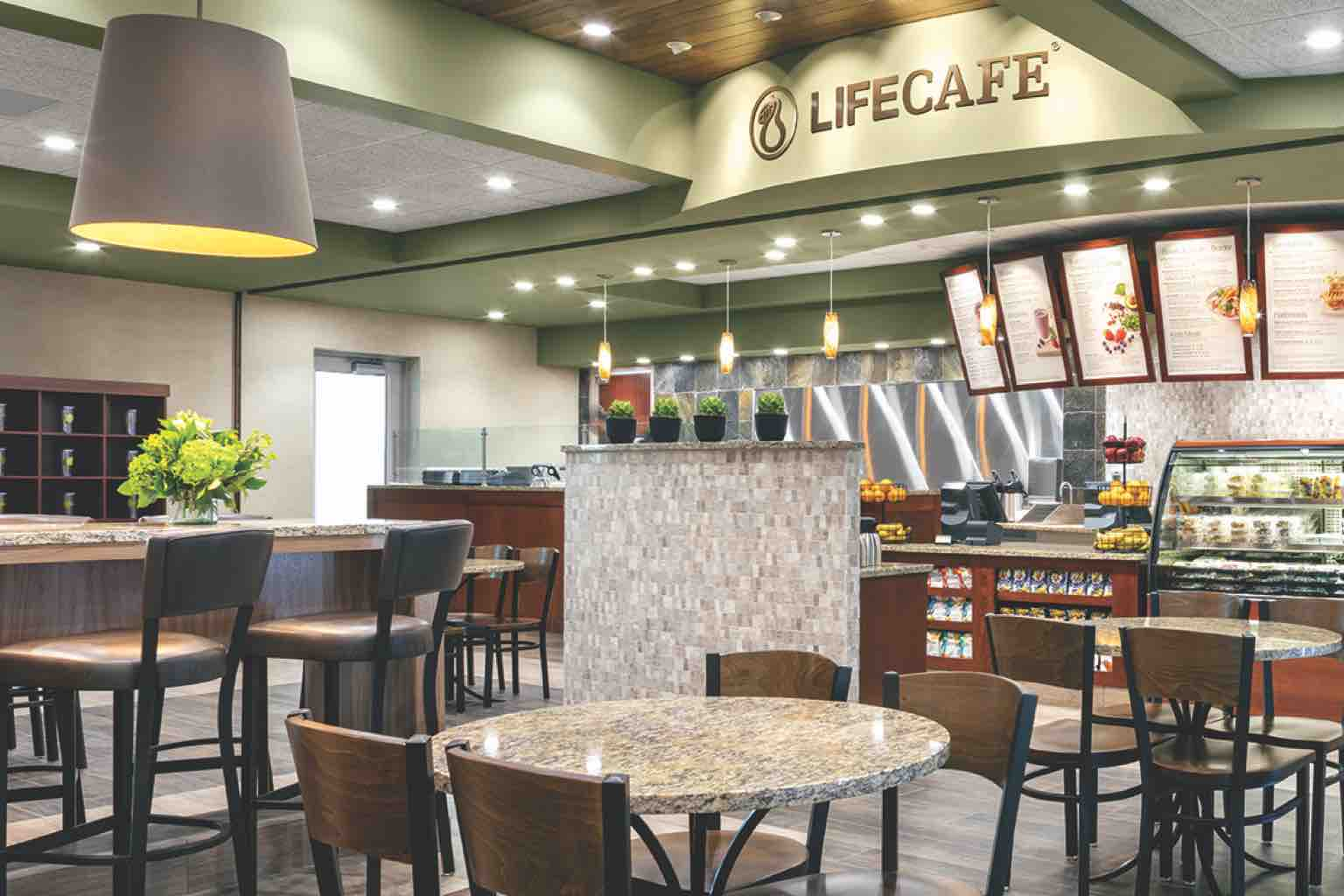 A Life Time LifeCafe featuring menu boards, a counter with a fresh food cooler and high- and low-top seating
