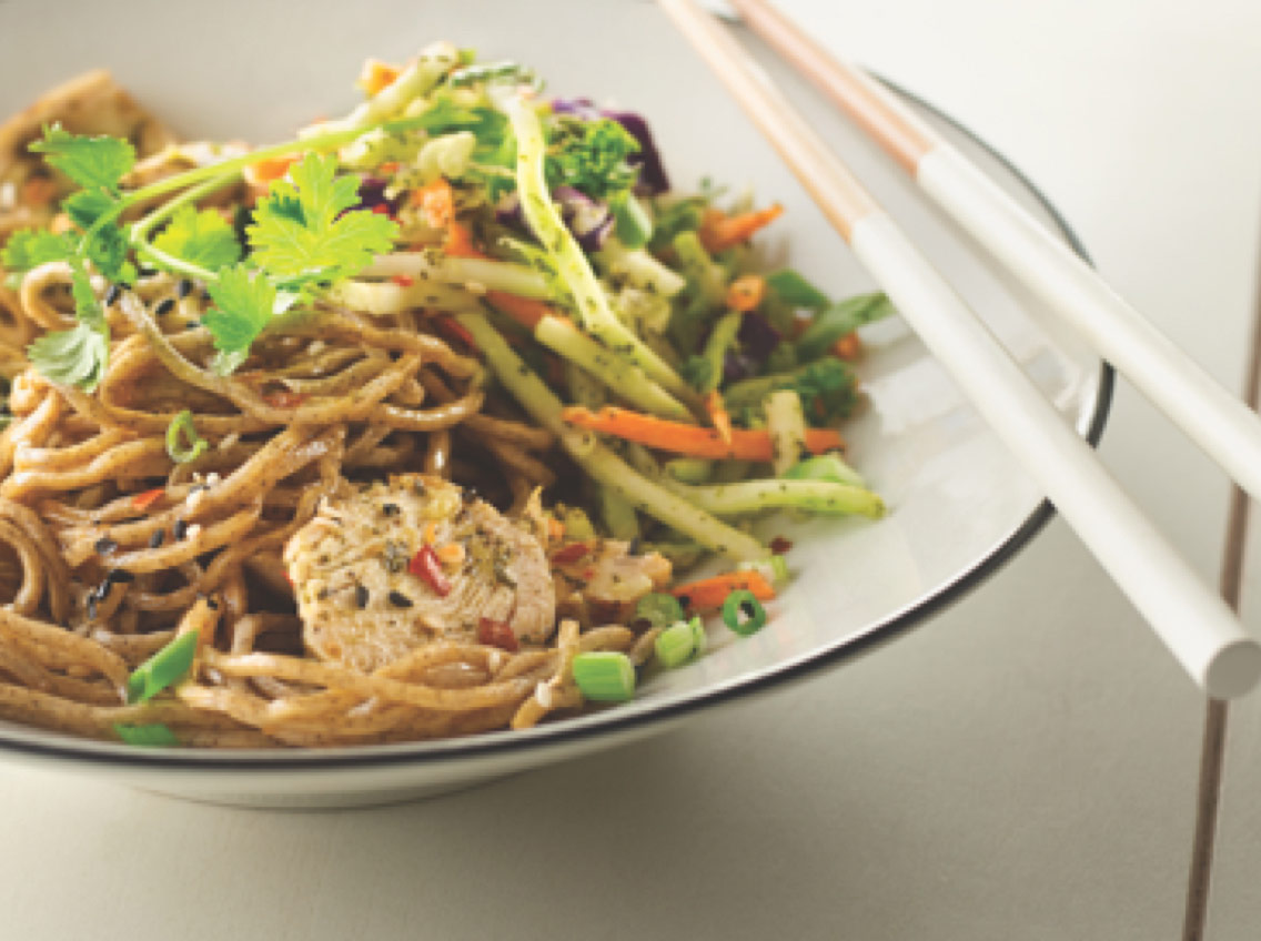 Vegetables, chicken and noodles in a bowl with chopsticks