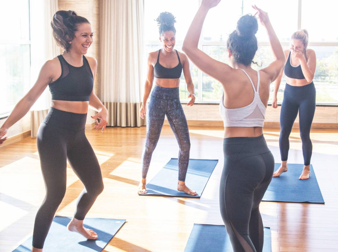 Four women laughing and dancing in a yoga class at Life Time