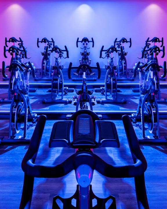Rows of indoor bikes in a cycle studio at Life Time with colorful lights