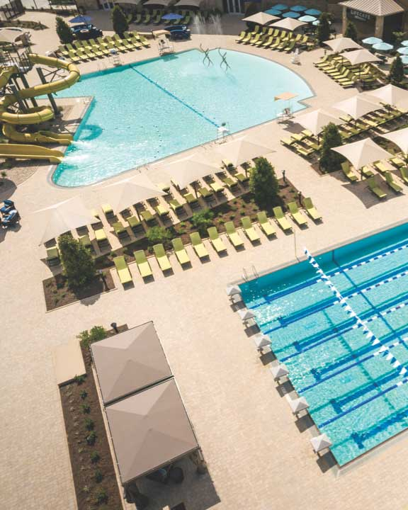 an aerial view of the outdoor pool deck with lap pool, leisure pool, deck chairs and water slide