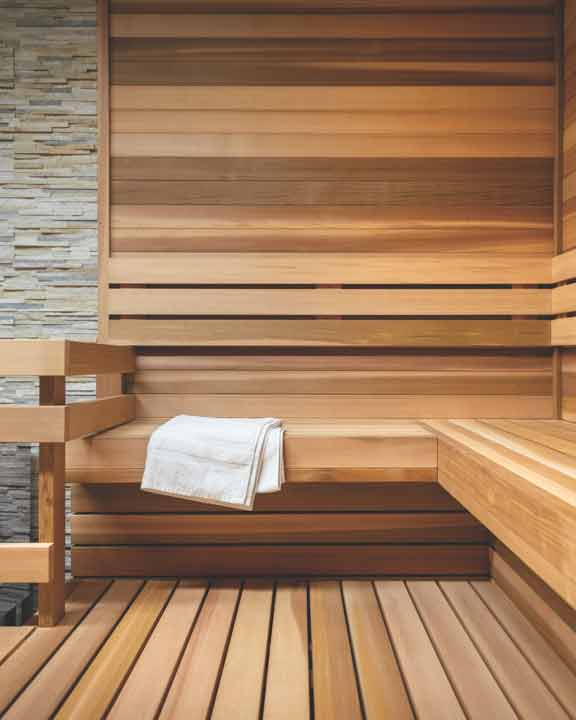 a wood and stone sauna room with lowel laid on the bench