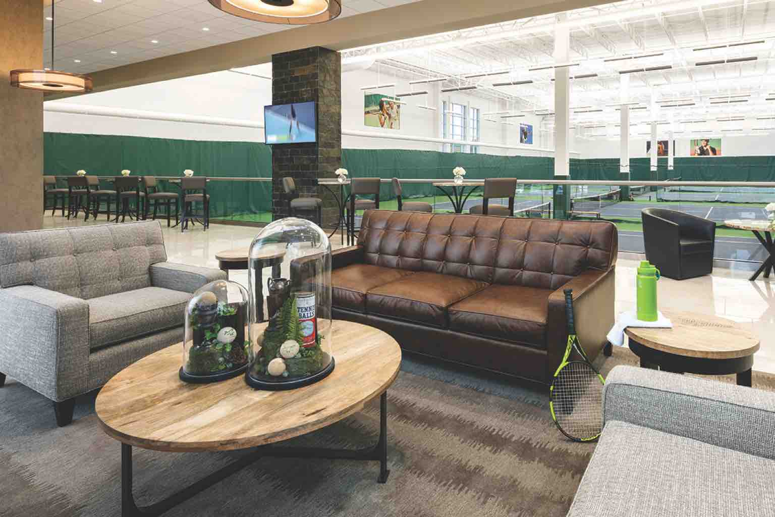A comfortable lounge area with sofas, chairs and tables overlooking several indoor tennis courts