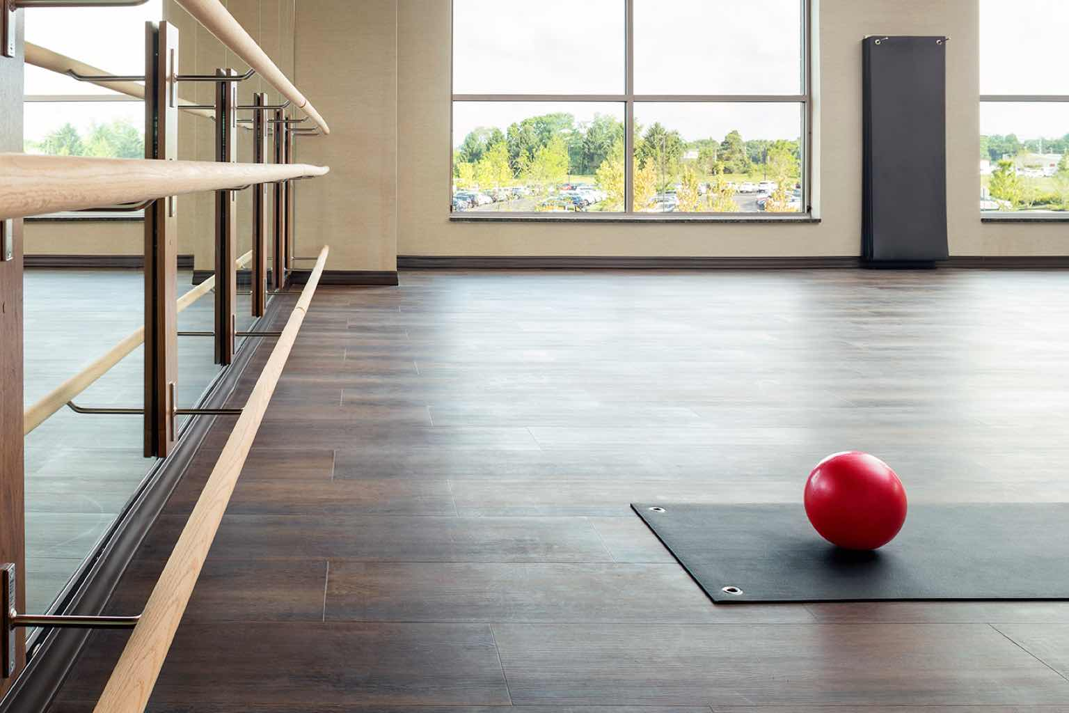 A red Pilates ball sits on top of a black yoga mat prepared for a barre class in a Life Time group fitness studio