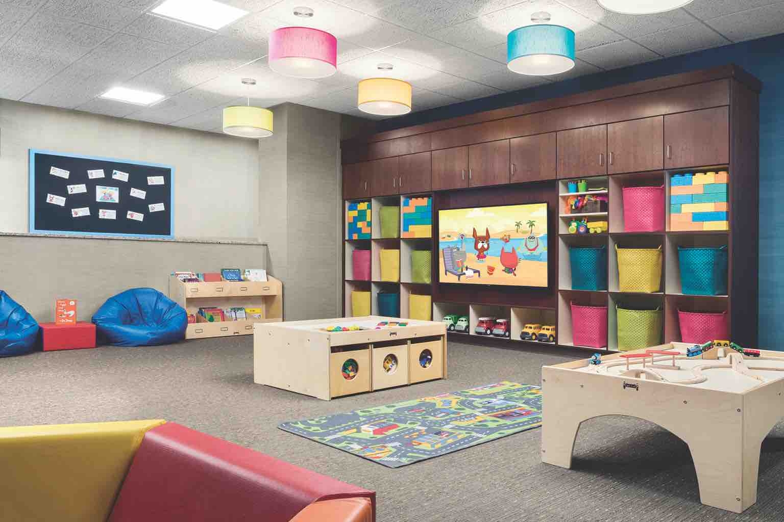 A child center with a large screen, bulletin board, colorful cubbies, activity tables and beanbag chairs