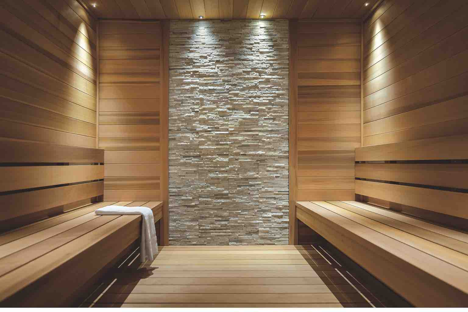 A pristine sauna with tile walls, wood floors and a wood bench holding a crisp white towel