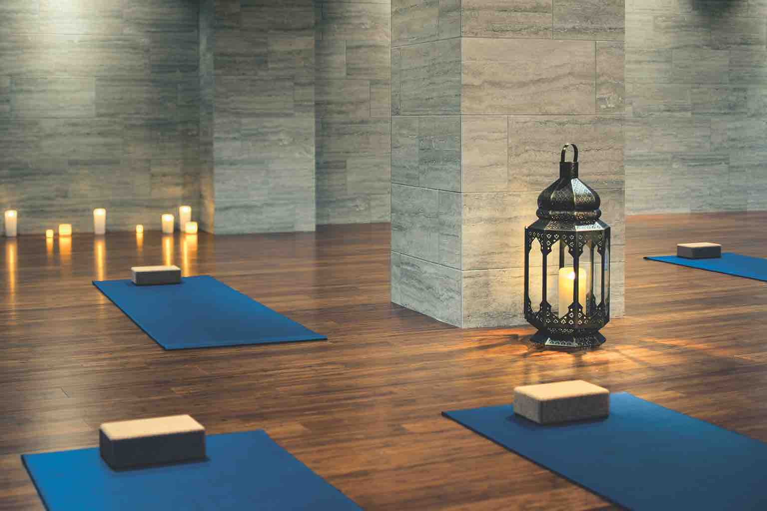 Blue yoga mats, each equipped with a yoga brick, lined up on the wood floor of a candlelit studio