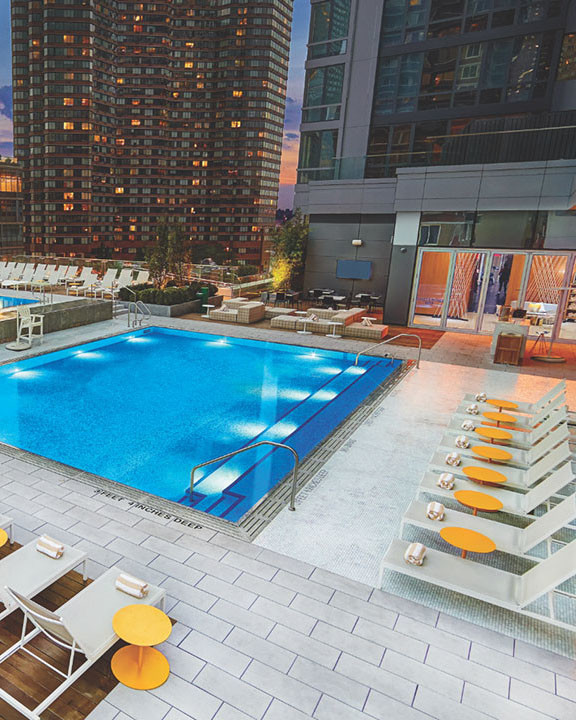 The rooftop pool deck with lounge chairs and tallk buildings surrounding it.