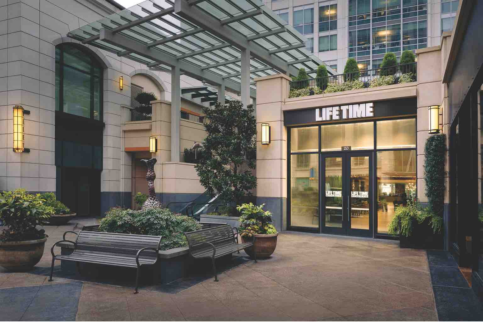 The cozy entrance to Life Time Bellevue, featuring park benches, patio pots and natural plantings