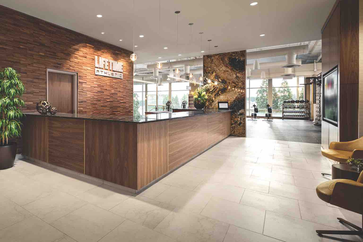 A large wooden reception desk in the lobby of Life Time Bellevue