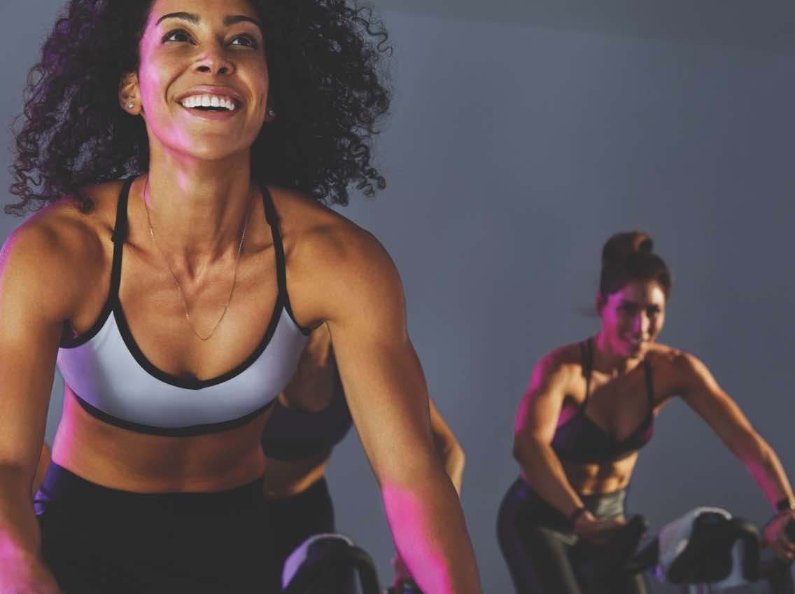 Two women smiling while participating in an indoor cycle class
