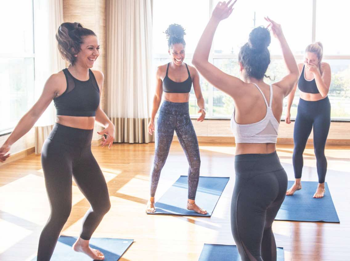 Group of women laughing and dancing in a yoga class at Life Time