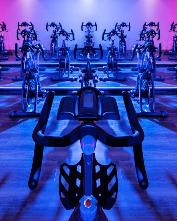 Large indoor cycle studio at Life Time with rows of indoor bikes and colorful lights