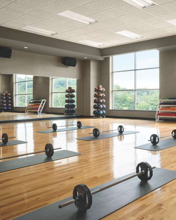 Mats and weighted barbells set out in rows in a group fitness studio