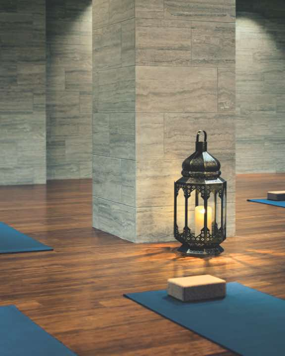 Candle-lit yoga studio with a shiny wood floor and two rows of blue yoga mats each equipped with a yoga block