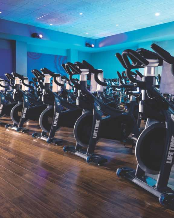 Colorfully lit indoor cycle studio with rows of indoor bikes