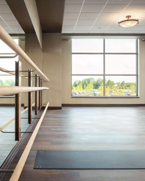 Sunlit group fitness studio with wooden floor, mirrored wall and barre