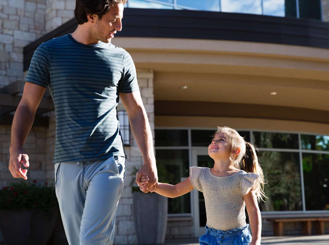Man holding hands with a female child while walking out of Life Time