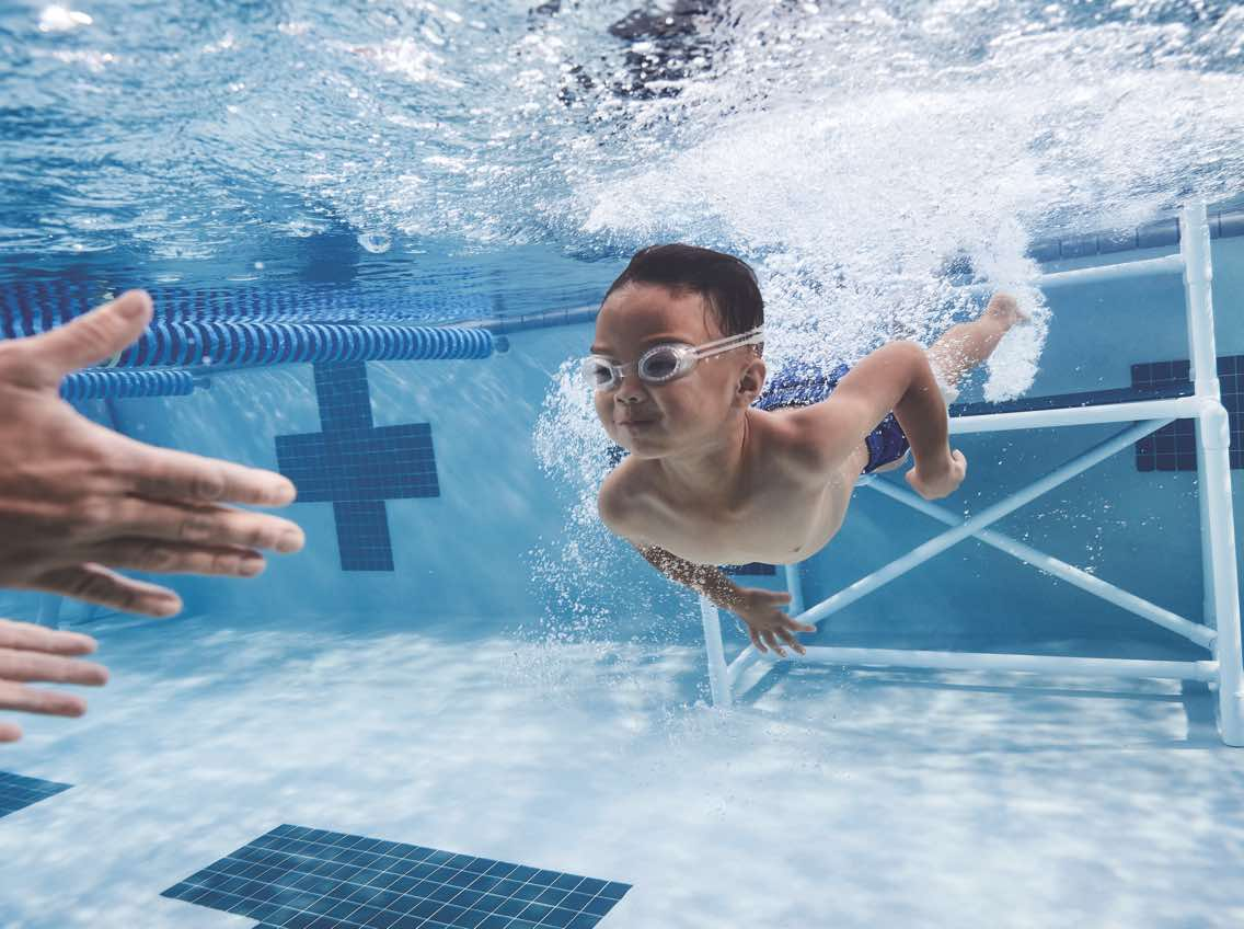 Underwater view of a male child swimming in an indoor pool