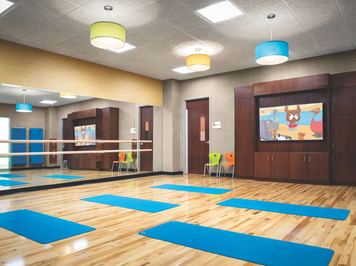 Kids activity studio with wooden floor and blue yoga mats