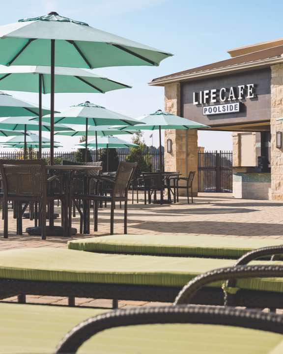 Outdoor pool area with lounge chairs, tables with umbrellas and LifeCafe Bistro