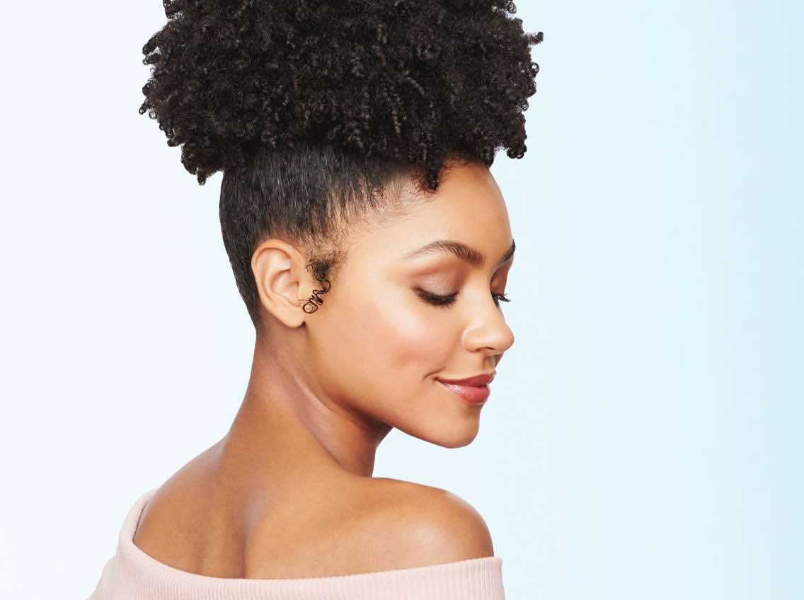 Woman with dark, course, curly hair pulled into a but on top of her head