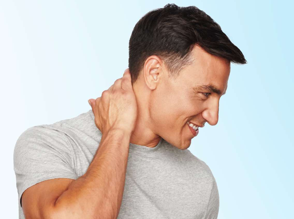 Man with short, dark hair rubbing his hand on his neck