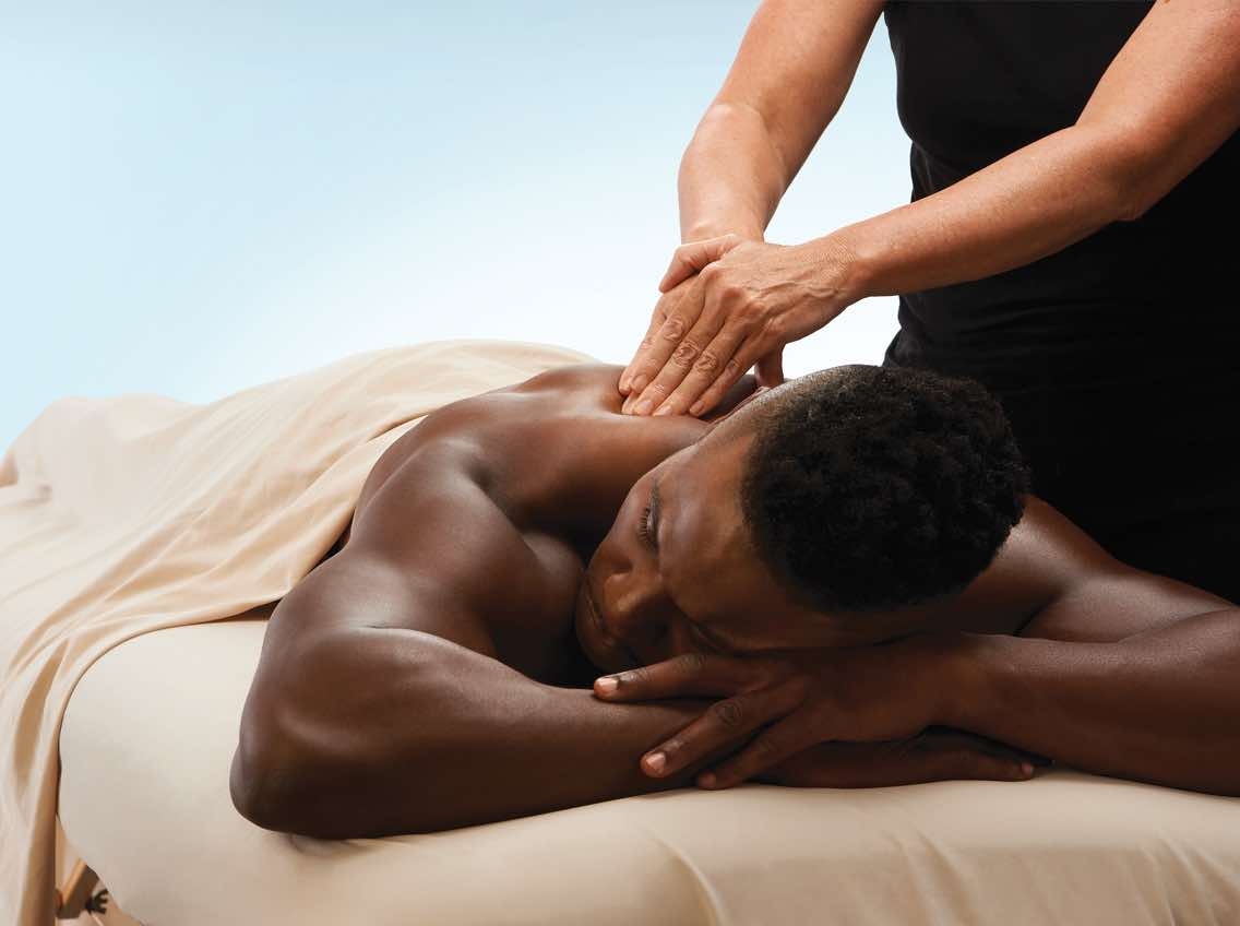 Man lying on a massage table receiving a massage from a massage therapist
