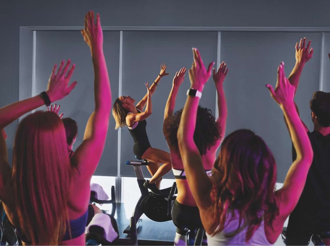 Group of people cheering on indoor bikes in an indoor cycle class