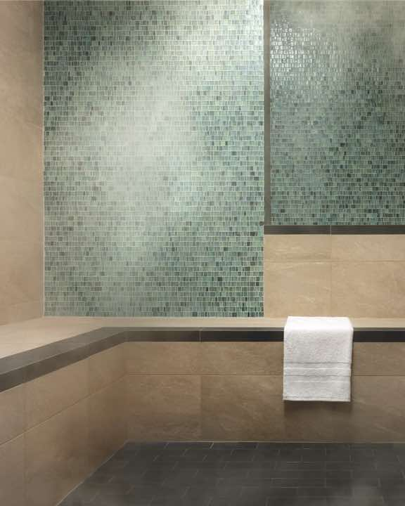 Peaceful steam room space with bench seating and tile walls