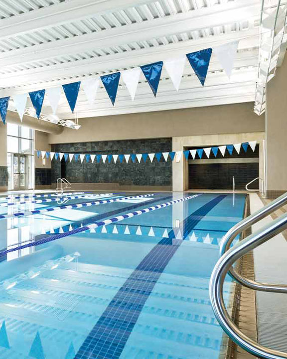 Indoor lap pool with five lap swim lanes and starting blocks at Life Time