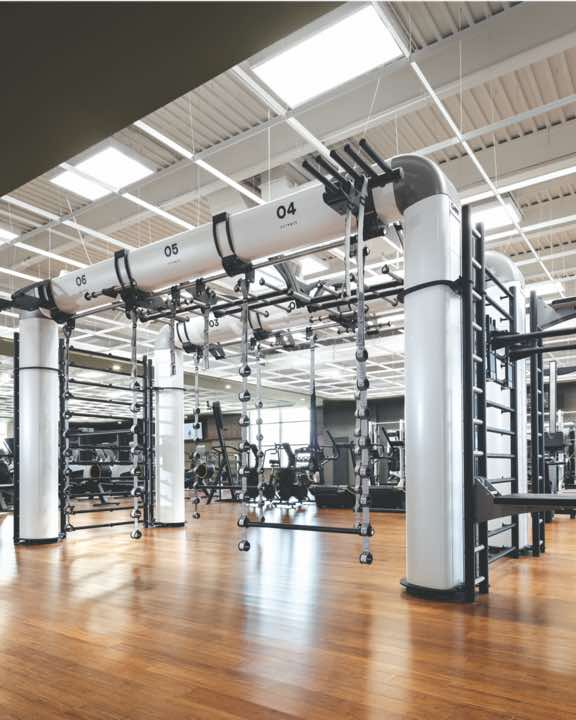 Expansive fitness floor with weight machines and racks of weights at Life Time