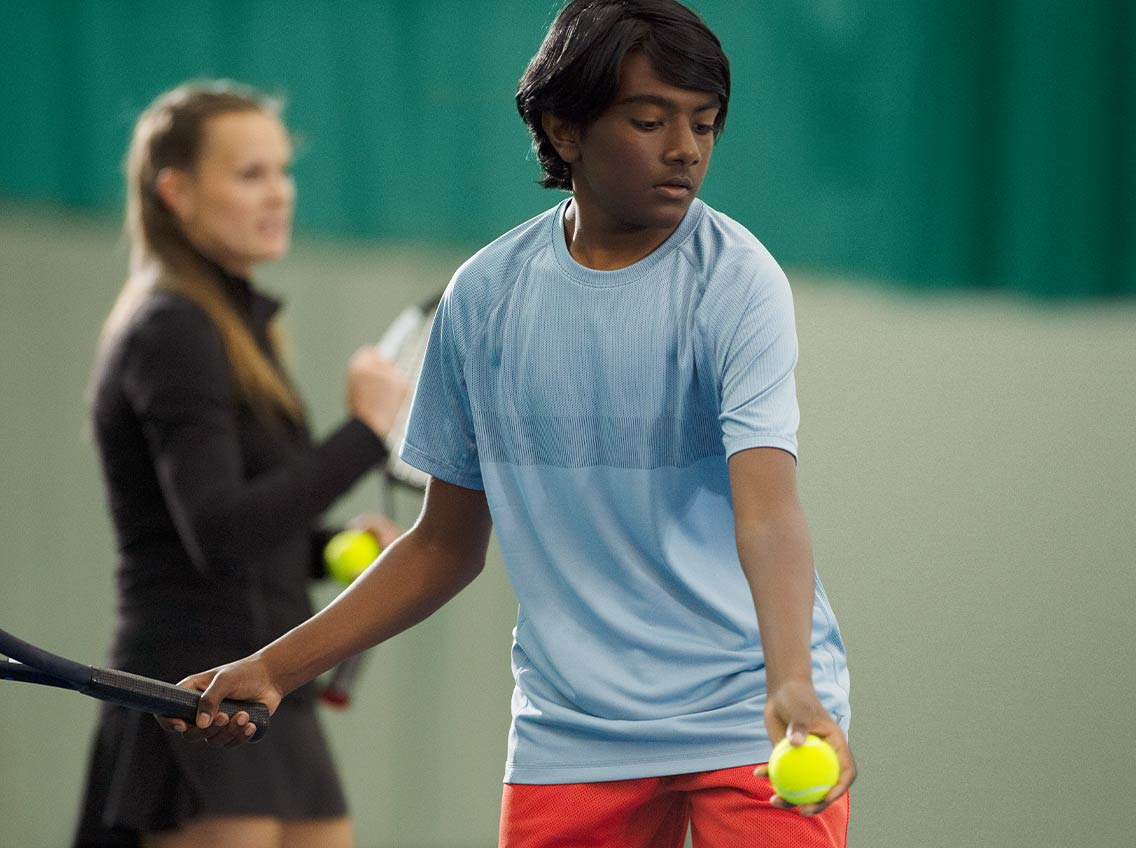 A teenage boy prepares to hit a tennis ball while a coach watches in the background